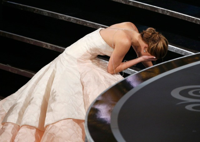 Jennifer Lawrence falls as she walks up the steps to accept the award for best actress at the 85th Academy Awards in Hollywood